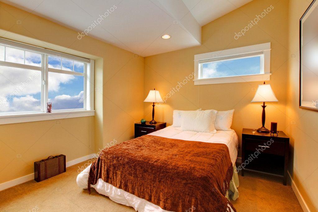 Interieur Slaapkamer Verven : Slaapkamer met gele mosterd verf en bruin beddengoed u stockfoto