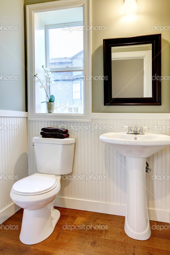 Small nice bathroom with green walls and cherry floor.