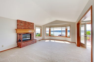 Bright living room with brick fireplace and deck view.