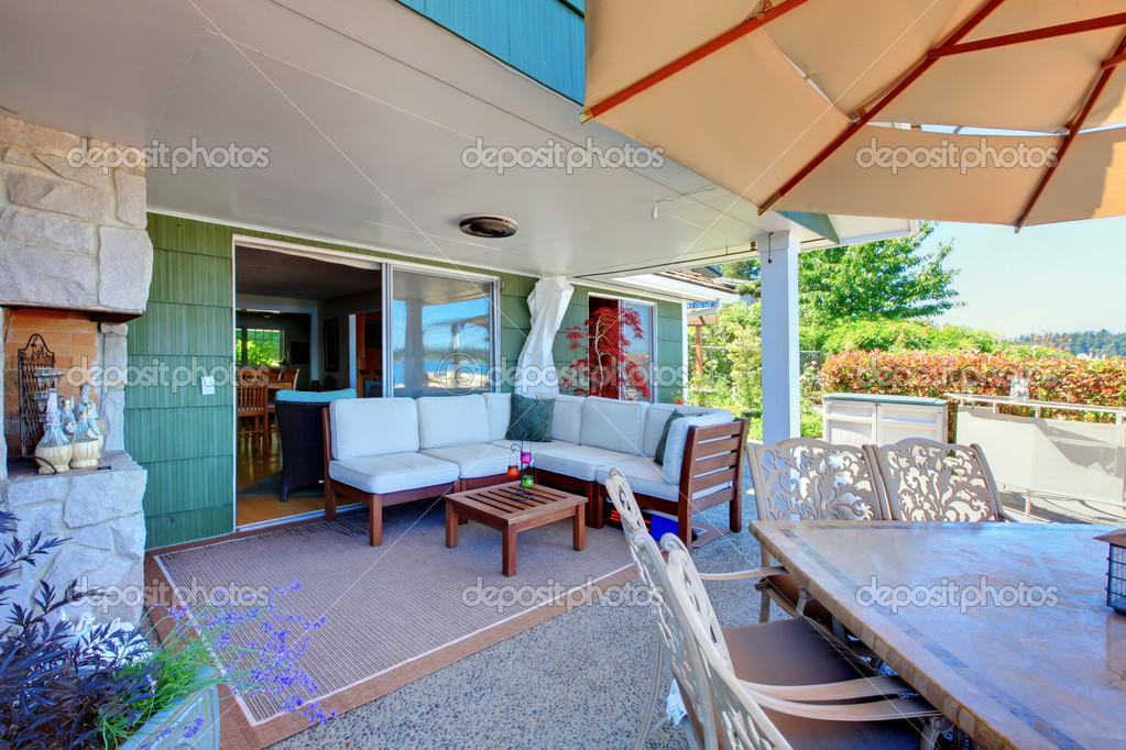 Outdoor covered living room area with sofa and table