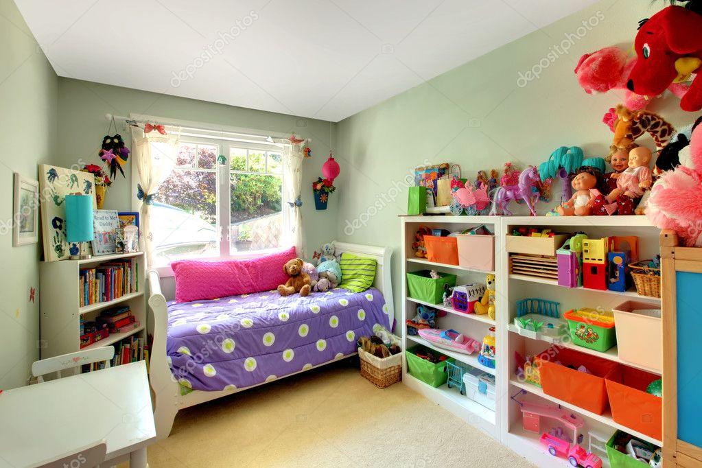Meisjes slaapkamer met veel speelgoed en paarse bed u stockfoto