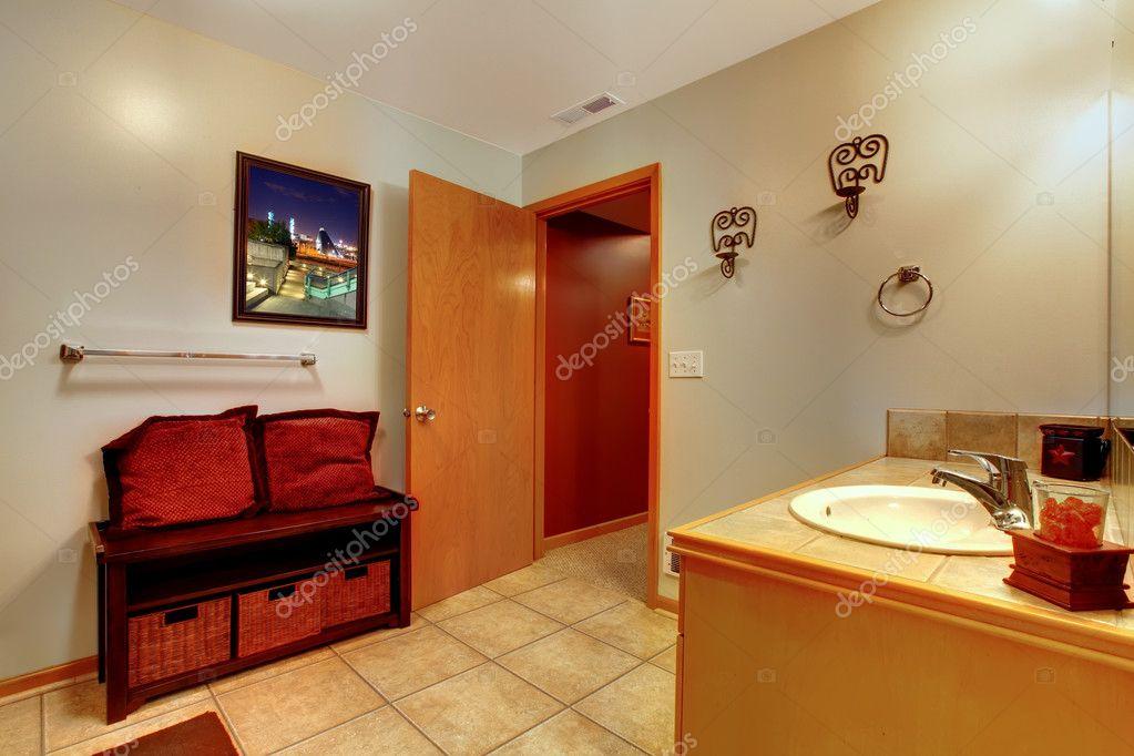 großes Badezimmer mit doppeltem Waschbecken und Badewanne mit roten ...