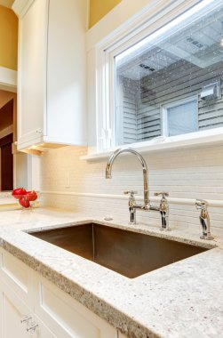 Large deep metal kitchen sink with granite countertops.