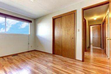 Empty bedroom with shiny hardwood floor.