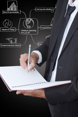 Businessman write on notebook with strategic plan.