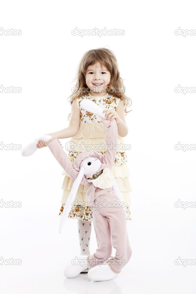 Portrait of a smiling little girl playing with a toy rabbit