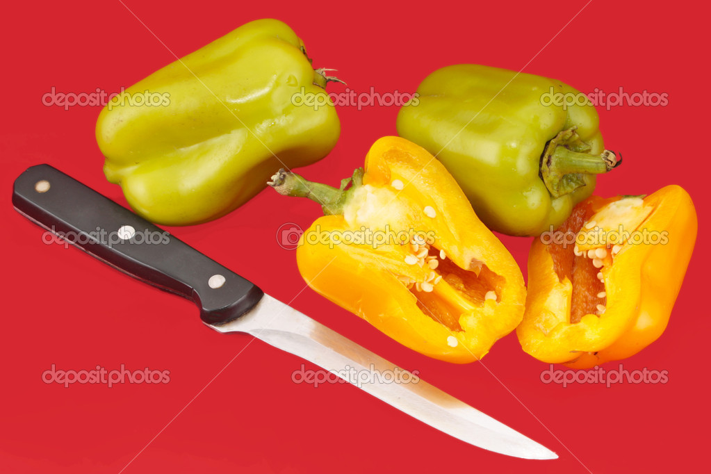 Paprika and knife on red background