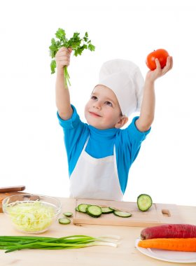 Little cook with parsley and tomatoes