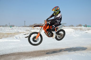 Motocross driver flies over hill out of snow