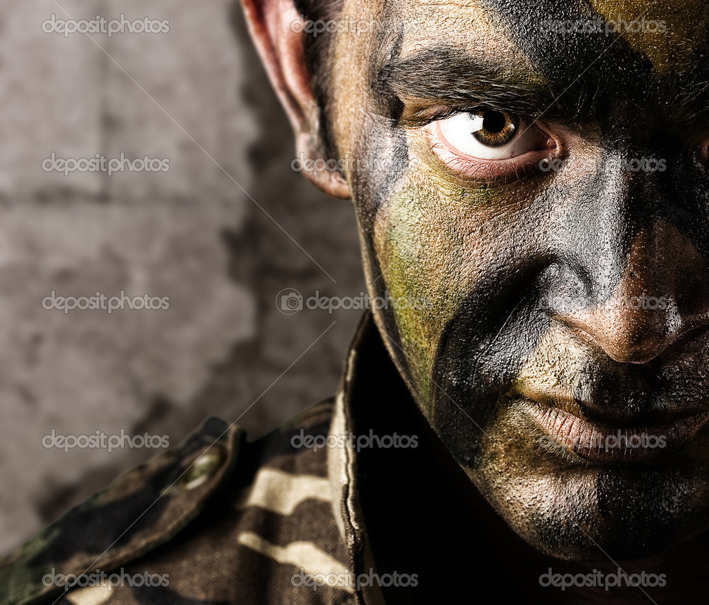 Young soldier face looking straight ahead againsta a grunge wall stock vector