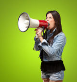 Photo Portrait of young woman screaming with megaphone against a green