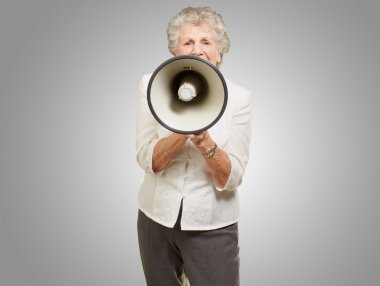 Portrait of senior woman screaming with megaphone over grey back