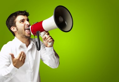 Portrait of young man shouting with megaphone over green backgro