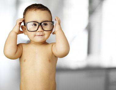 Portrait of funny kid shirtless wearing glasses indoor