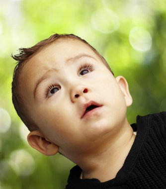 Portrait of a handsome kid looking up against a nature backgroun