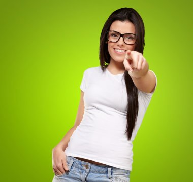 Portrait of young woman pointing with finger against a green bac