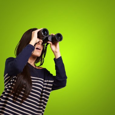 Portrait of young girl looking through a binoculars over green