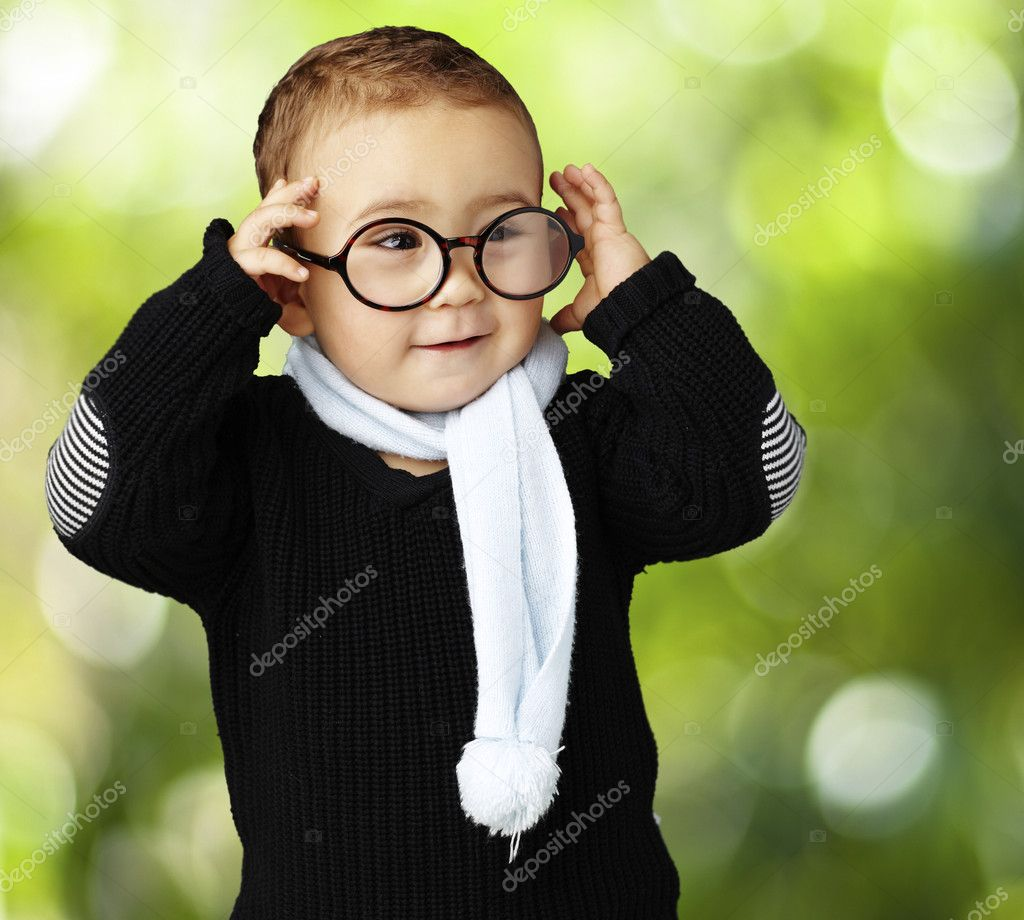 Portrait of funny kid holding his glasses against a nature back