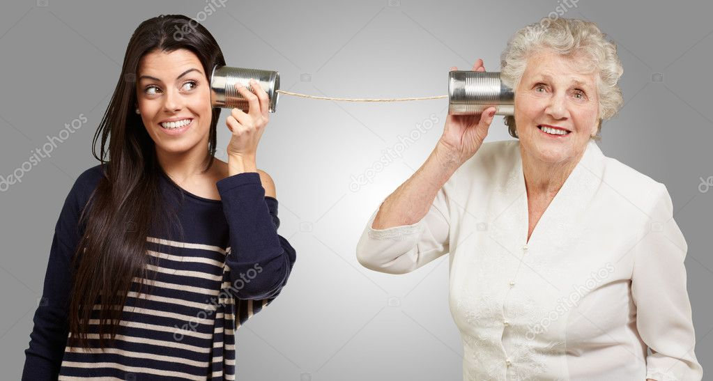 Portrait of young girl and her grandmother hearing sounds using