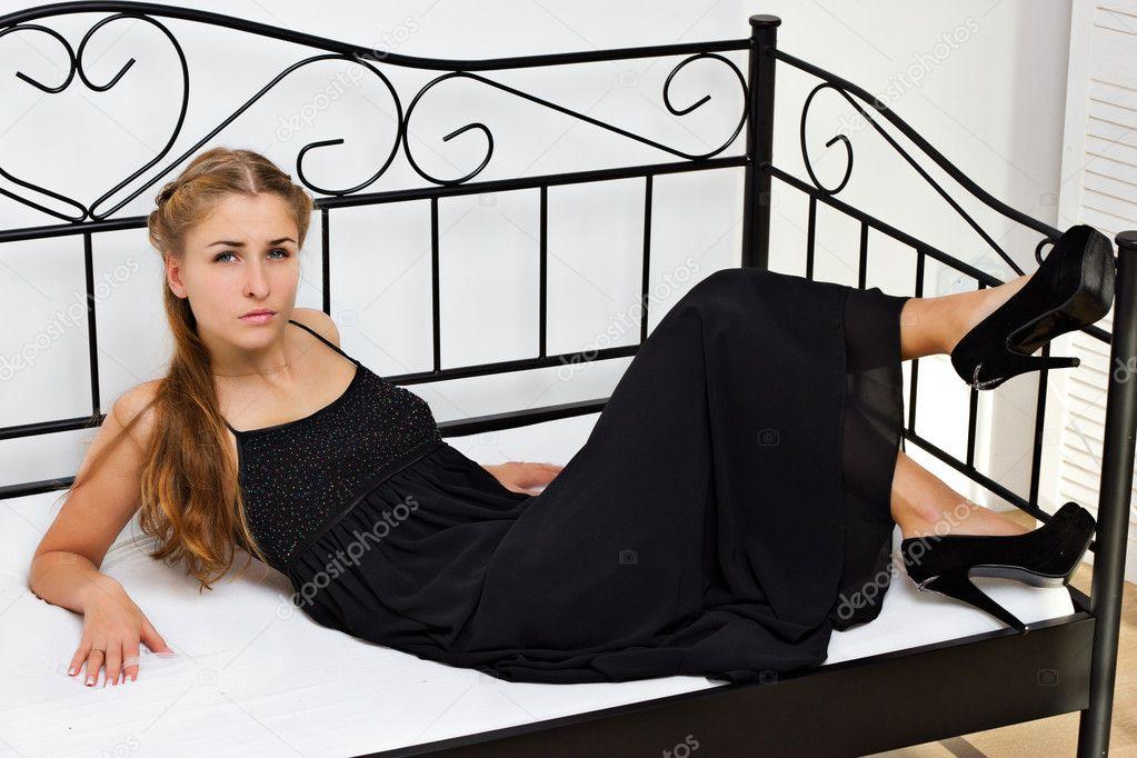 m dchen im schwarzen kleid schuhe mit high heels auf dem bett liegend stockfoto victoshafoto. Black Bedroom Furniture Sets. Home Design Ideas