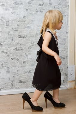 The little girl measures the mother's shoes with heels