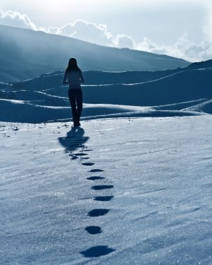 Lonely woman silhouette at winter mountains