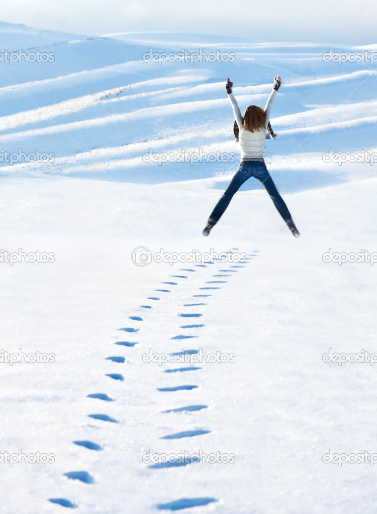 Happy woman jumping at winter mountains