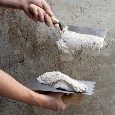 Construction notched trowel and worker hands
