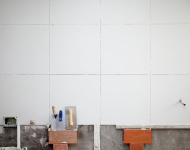 Tiles white wall contruction with trowels tools