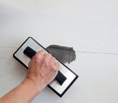 Grouting tiles with rubber trowel man hand