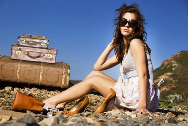 Young traveling woman with her suitcases long the road