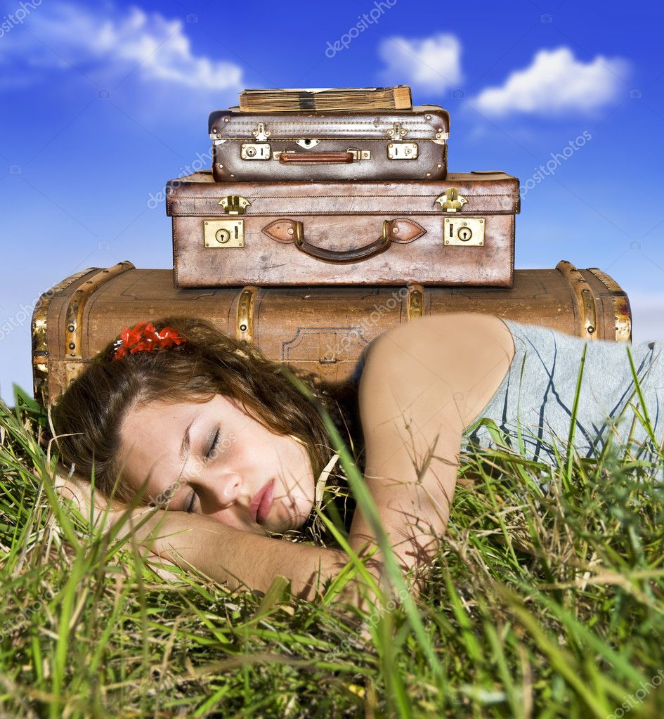 Traveling young woman resting in a field with her suitcases