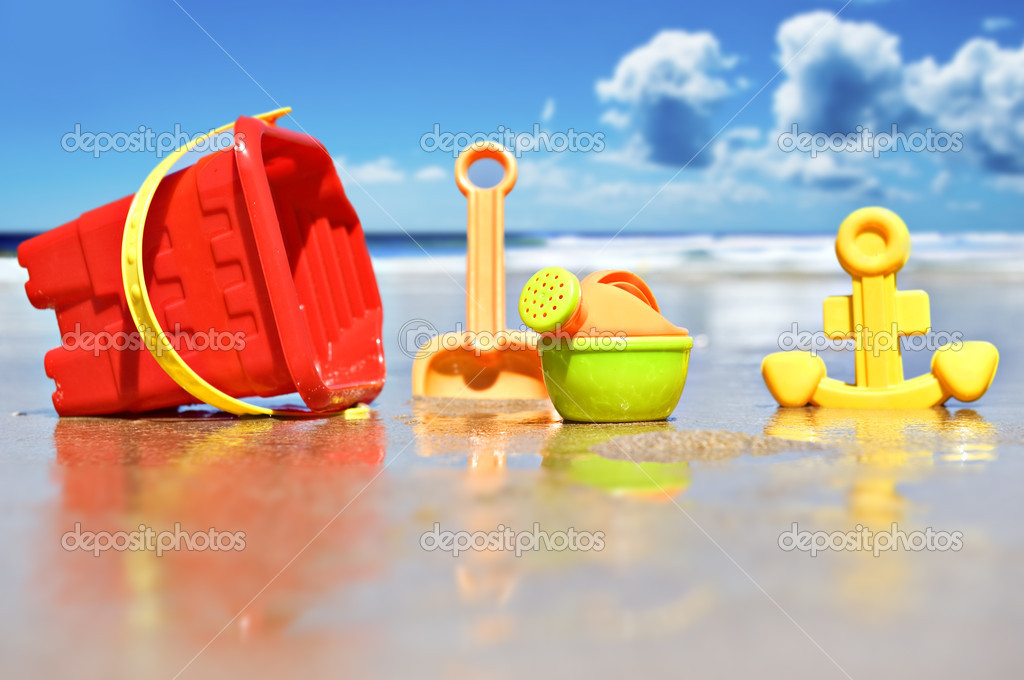 Closeup of children's beach toys at the beach - focus on watering can