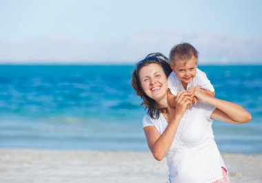 Young mother and her son playing at beach
