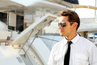 Handsome man, a serious captain in a white shirt near the yacht,