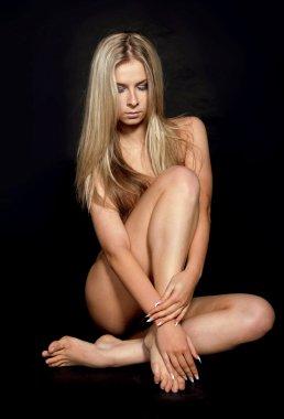 Sexy naked model Sitting isolated on black studio background