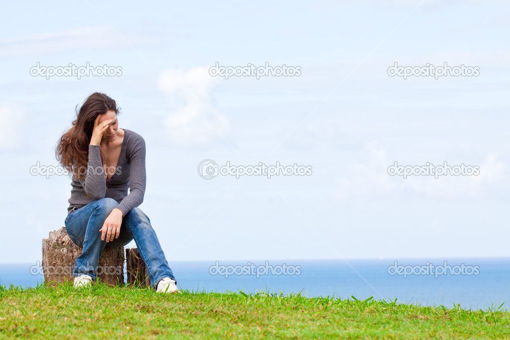 Depressed, sad and upset young woman sitting outside