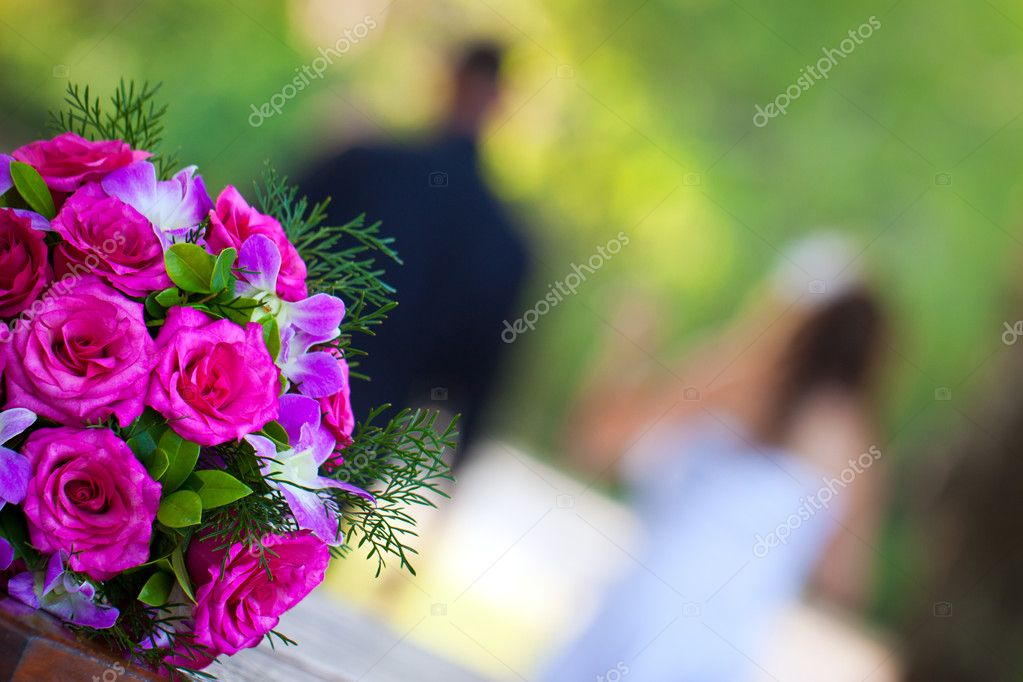 Newly wed couple walking away from a beautiful bridal bouquet