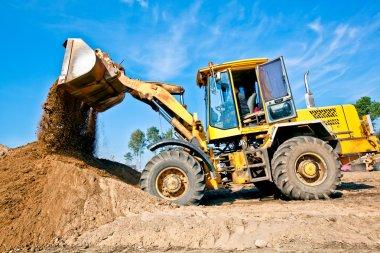 Wheel loader unloading soil at construction site
