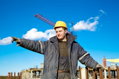 Industrial worker gives instructions to construction workers
