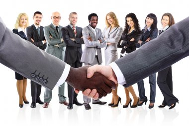 Shaking hands and business team formed of young businesspeople