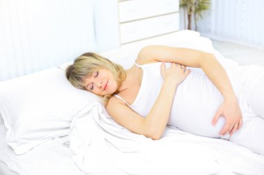 Sleeping pregnant woman on bed