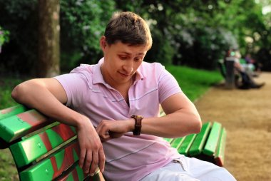 A young man looks at his watch on his arm and sits on a bench in the park and waiting for meeting