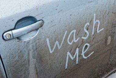 Inscription wash me in the car door