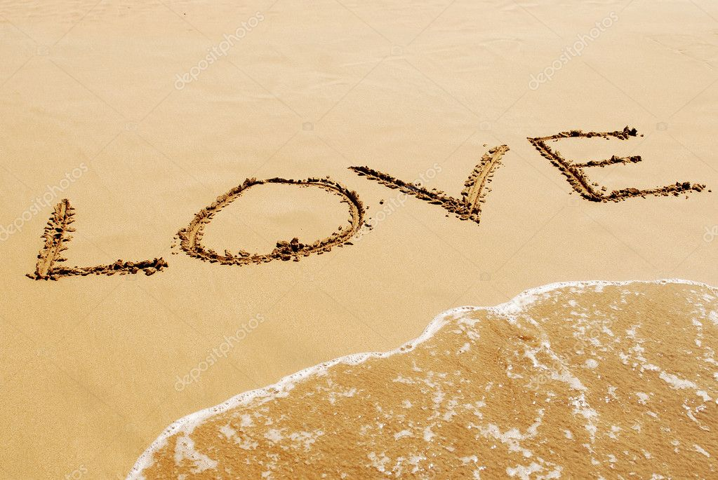 The inscription on the sand near the sea and the waves - LOVE.
