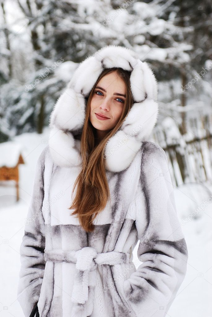 Young Beautiful Girl In Fur Smiling, And Walking Through