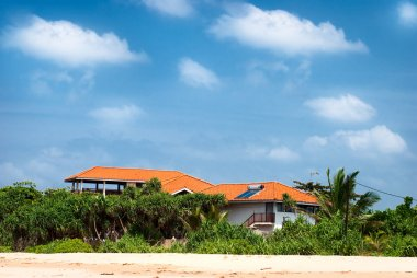 Beach house with solar panels and tropical vegetation with the blue sky
