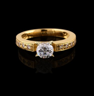 Gold ring with brilliant on black background