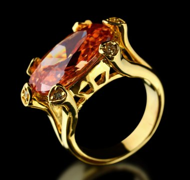 Gold ring with gem on a black