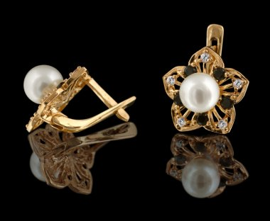 Gold earrings with diamonds and pearl isolated on black